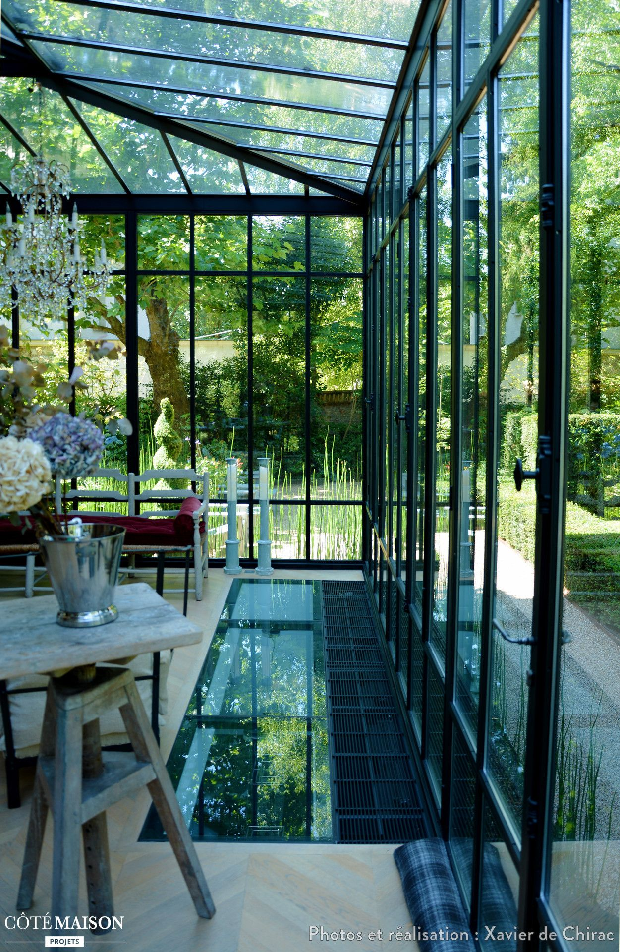 Une v randa luxueuse donne vue sur un jardin luxuriant Verriere jardin