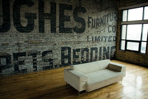 Loft with a brick wall very cool with a ghost sign painted on a brick wall priceless