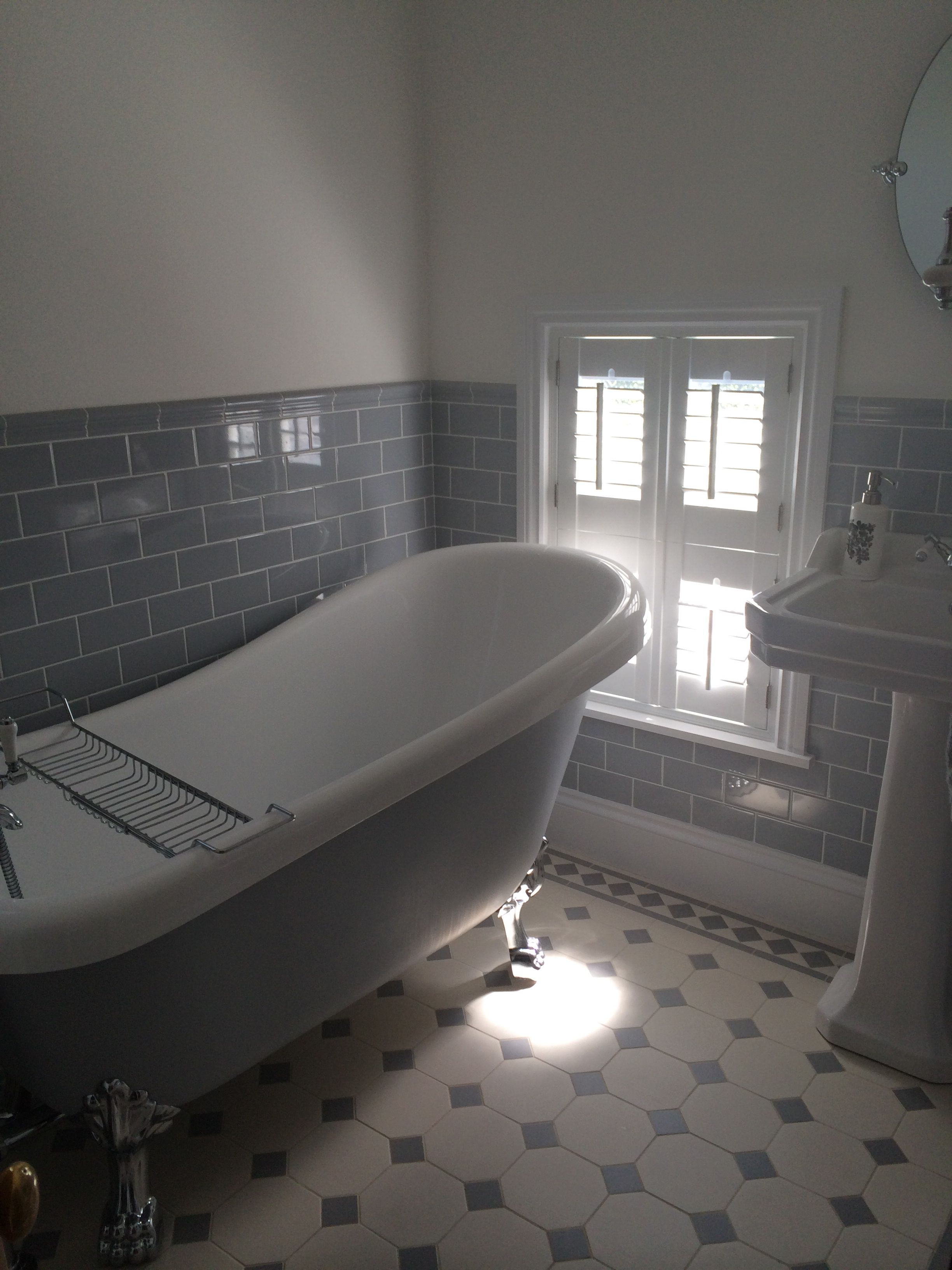 Grey and white bathroom. Painted roll top bath and