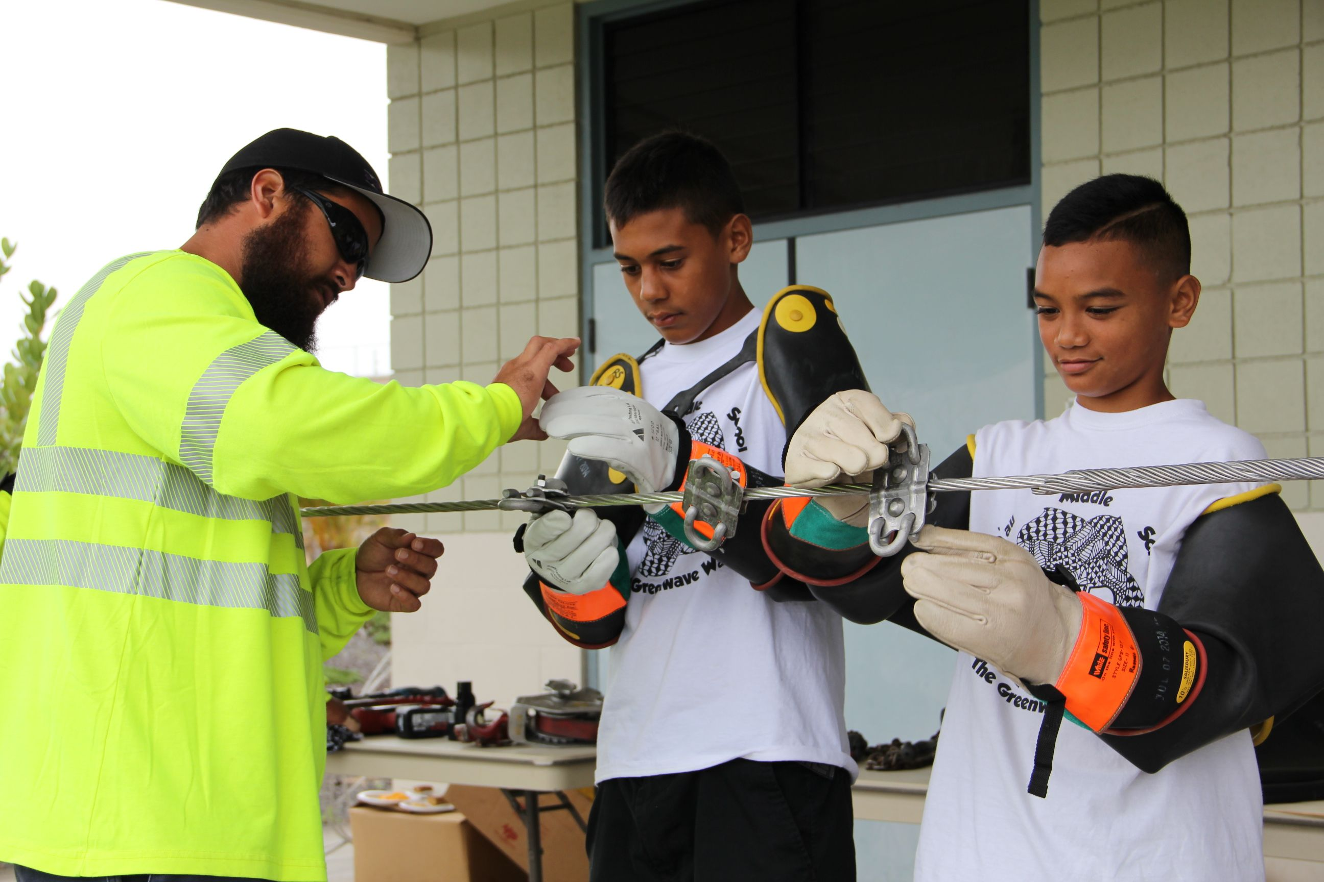 Hawaii Electric Light employees help students try on PPE