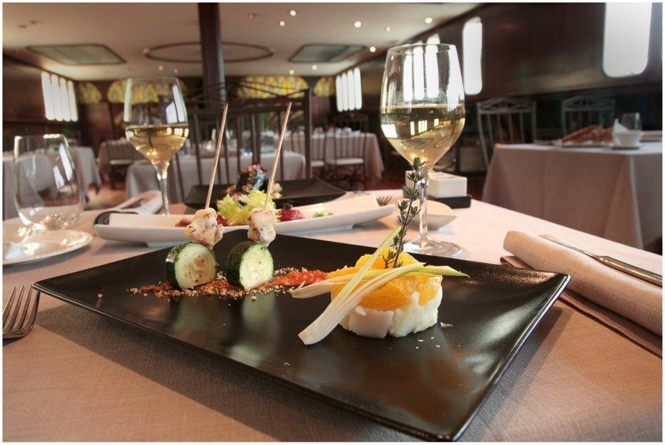 Timbal de bacalao confitado, patata, cebolla tierna y naranja.  Brocheta de rape y Calabacín con salsa de romescu de avellanas.