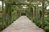 Photo of This charming walkway through the walled garden is framed by a timber pergola. T …