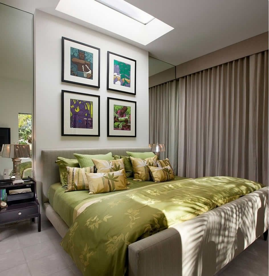 Bedroom wall pictures white concrete wall green bad cover green soft blanket green soft pillow gold table lamp soft cream draperies gray laminated wooden Fall asleep under