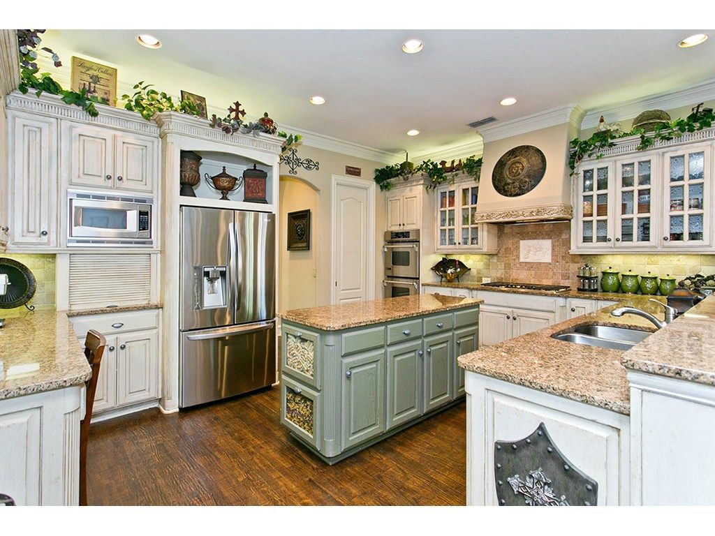 This look of contrasting cabinetry is so on trend // Green island, white outers plus granite and stainless
