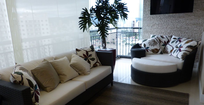 O amplo espaço da varanda facilitou a criação de um ambiente ideal para relaxar. O sofá e o chaise, de cores escuras, contrastam com as cores claras do piso e da parede. Projeto da arquiteta Nilce Nápoli.