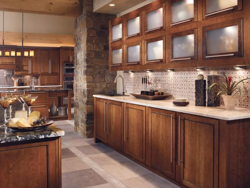 A Kitchen With Dark Cherry Cabinetry And Light Stone Counters Floors Cognac Finish On Coordinates Stylishly Stainless