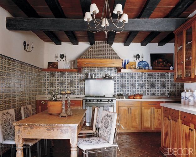 Renovated a kitchen in San Miguel de Allende, Mexico. The walls are sheathed in Talavera tiles, the floor is paved with stained brick tiles, and the antique farmhouse-style table is surrounded by Casamidy chairs.