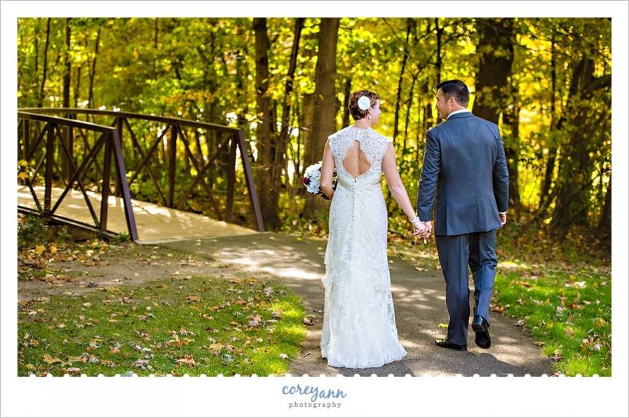 wedding picture locations akron ohio%0A Bride and Groom walking towards a bridge in the forest at Hubbard Valley  Park in Seville
