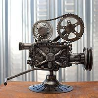 Auto parts sculpture, 'Rustic Film Projector' -- Armando Ramírez revisits the golden age of film with this classic film projector, built from various auto parts and pieces of scrap metal. Spark plugs, a pulley from a toy train engine, and the chain and wheel of a motorcycle begin to shape the projector. Several auto parts complete it, such as the ignition wheel of a car, the foot and diaphragm of the clutch pedal, and a bearing from the electrical system.