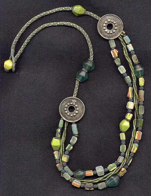 by Katie Singer | Necklace; old Chinese earplugs (low-grade silver), Majapahet glass burial beads, 1,000 years old, Afghani glass and jade, silver from India    handwoven cord | {Price not published, please contact seller}
