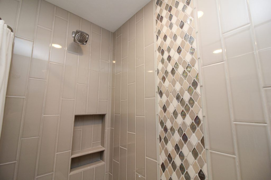 taupe tiled shower with mosaic tile accent strip  shower tile