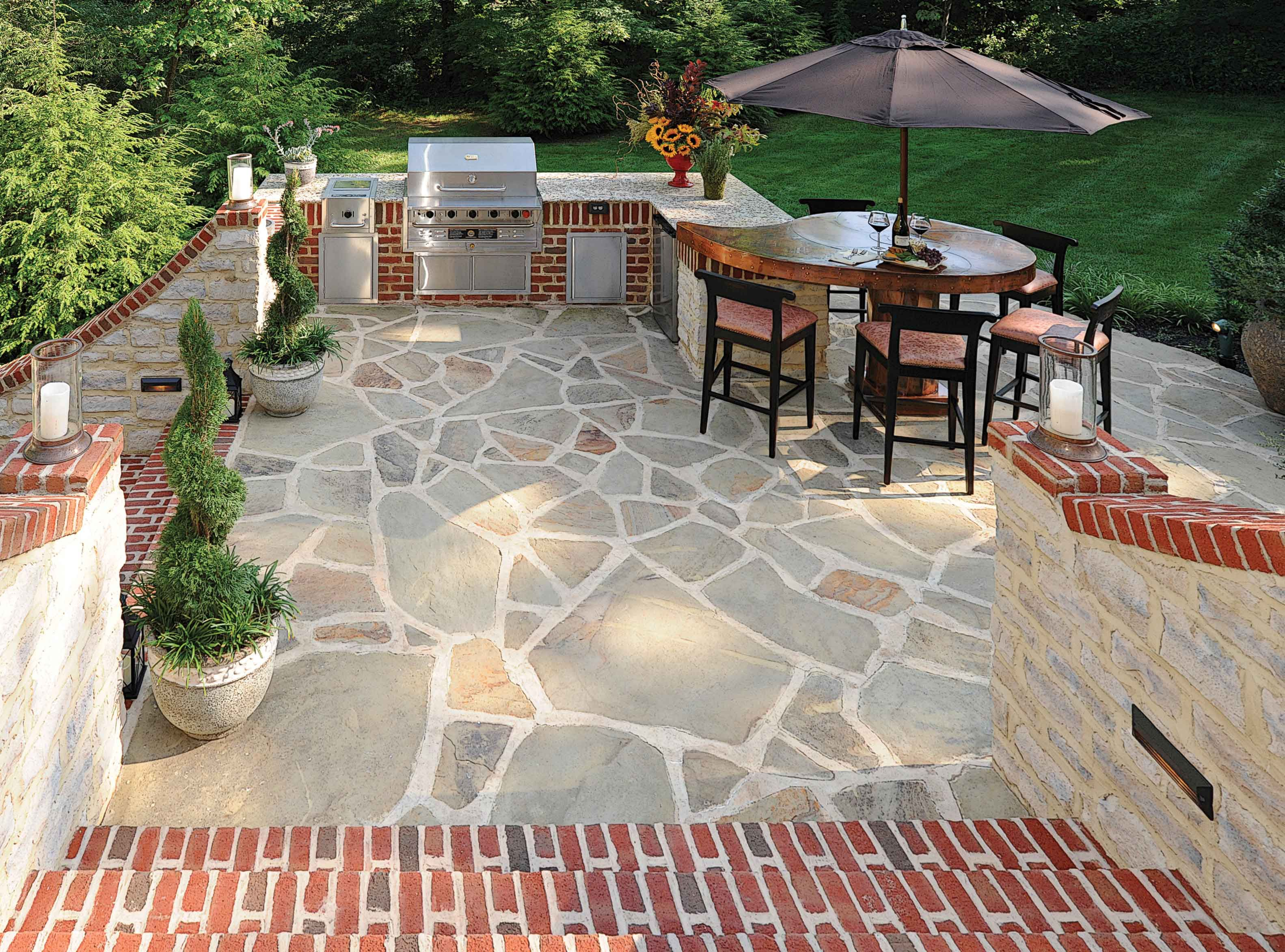 Red brick with gray mortar provides a nice visual punch to this beautiful  flagstone patio from