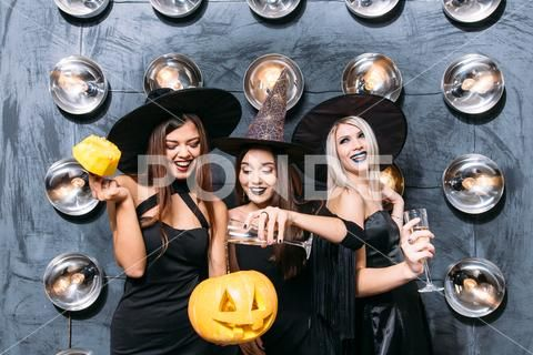 Three emotional young women in halloween costumes on party with pumpkin Stock Photos ,#women#halloween#emotional#young