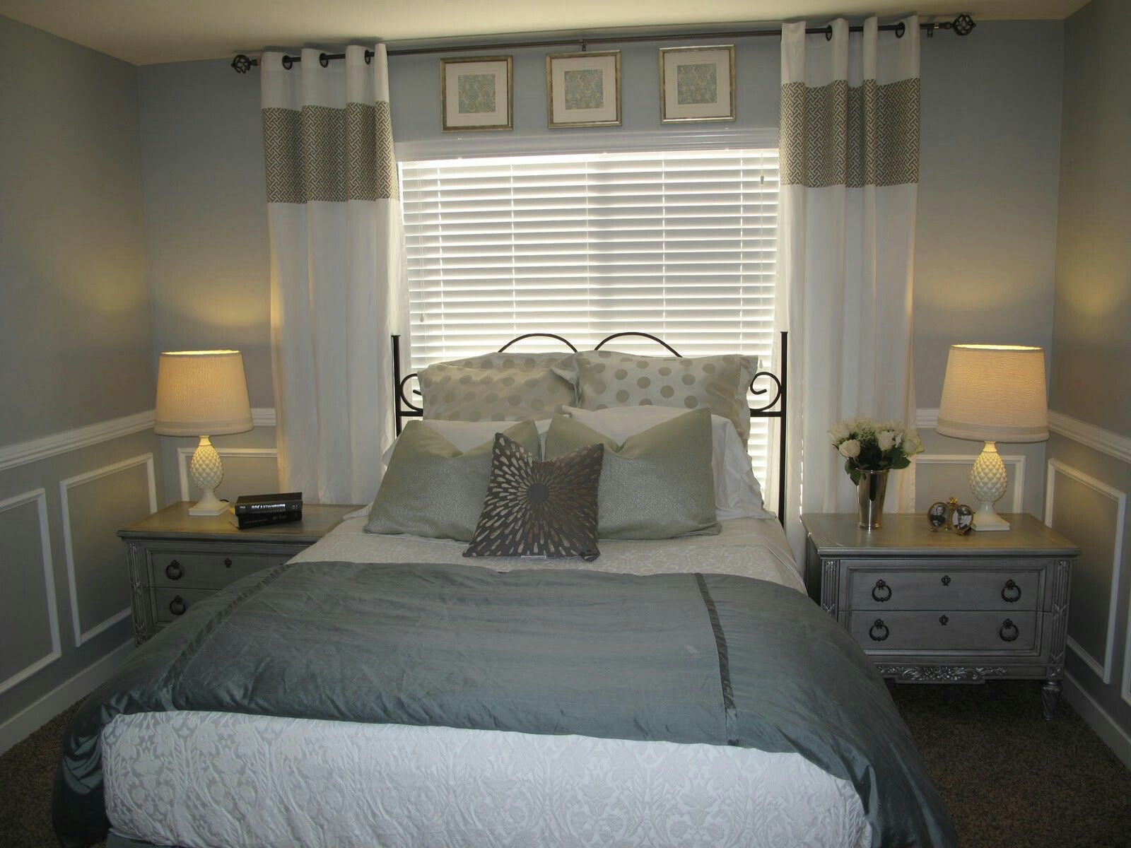 Curtains mounted high and wide with place to hang pics above window