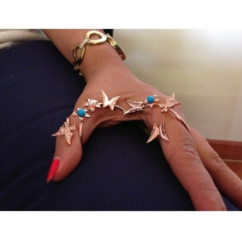 This is a simple gorgeous piece to be worn for the fancier occasions. Graceful in it's creation  http://www.ananasa.com/moveable-double-finger-ring-with-blue-stones-and-butterflies.html