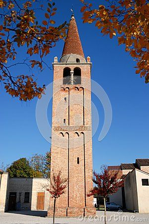 Photo made at the church bell tower of Vigo a town in the province of Padua in Veneto (Italy). In the image we see, in the foreground, with the bell tower at the tip cone framed by the leaves of the branches of two trees, over the bell tower you can see a few low buildings and a car parked in front of one of them and finally the intense blue of the sky.