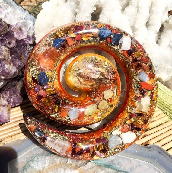 A Violet Flame Orgone Crystal plate intended to super charge your powers of manifestation across space and time. I poured this spiral plate over 4 hours, placing each crystal by hand, while chanting healing mantras. A powerful orgonite feng shui tool and beautiful altar piece for your home. A large double terminated Epidote included quartz point rests in the center of this organite plate. Pieces of realgar, Imperial golden topaz, dumortierite, tigers eye, red jasper, garnet, sphene, mookaite…