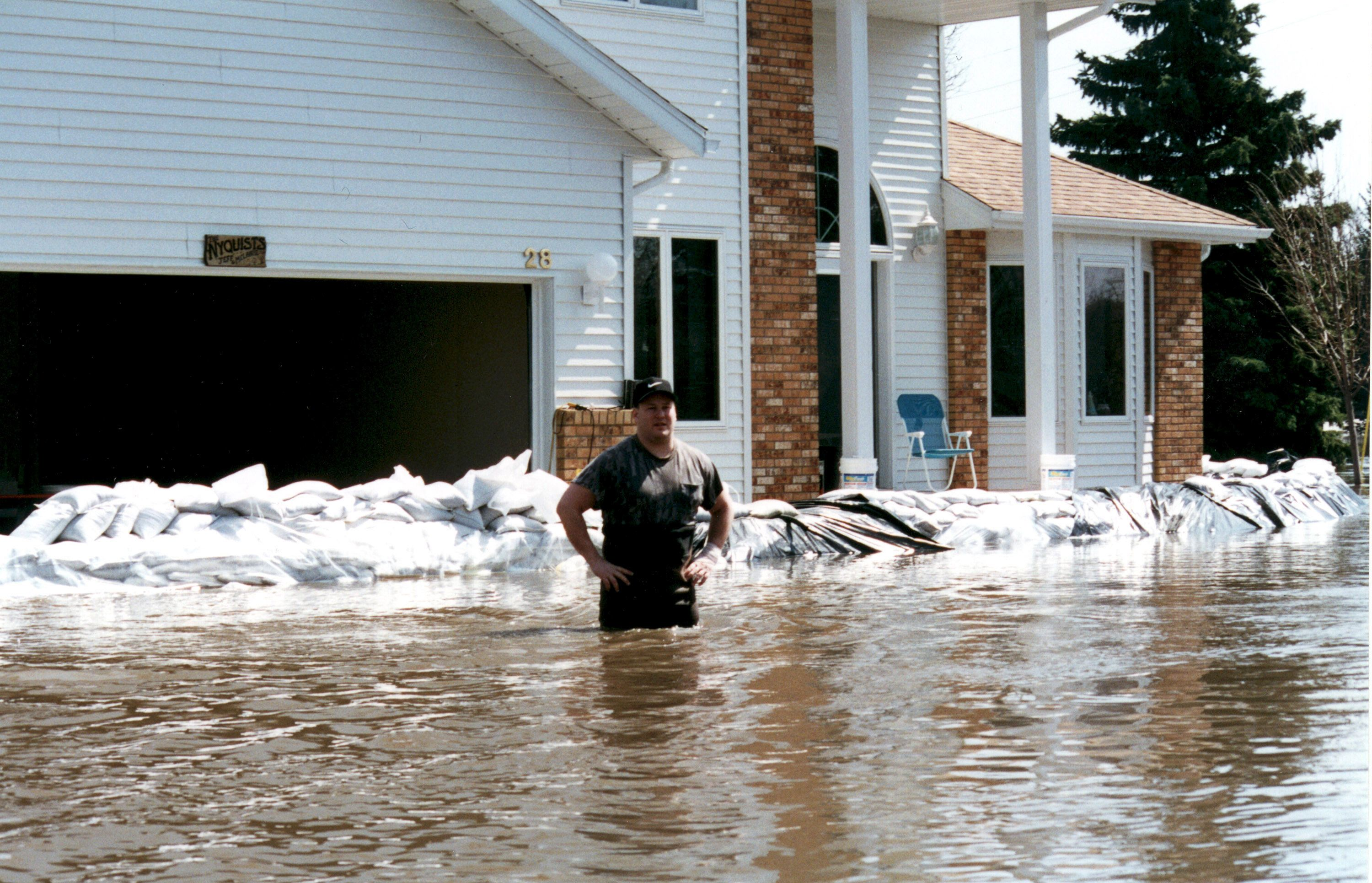 Man Standing In Front Of New Home In Water Up To His Hips House