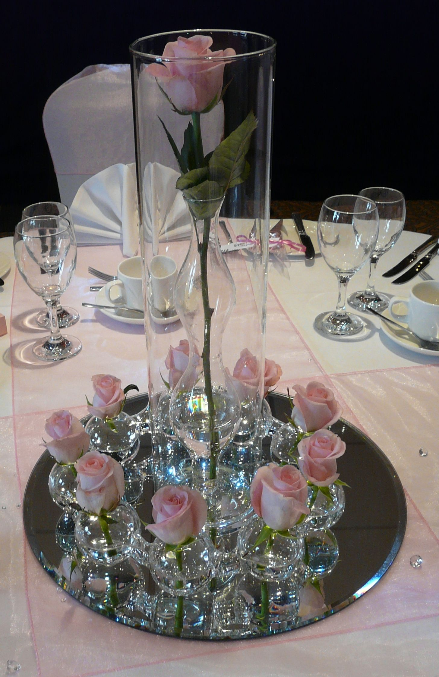 Round Mirror Tall Vase With Pink Rose And Small T Light Holders Heads In Each