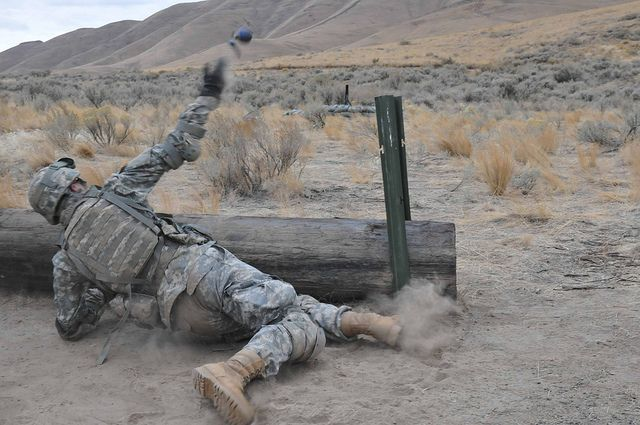 A cavalry trooper from A Troop, 2nd Squadron, 14th Cavalry Regiment, 2nd Stryker Brigade Combat Team, 25th Infantry Division, tosses a training grenade from behind cover during hand grenade training on Oct. 14 at Yakima Training Center, Washington.