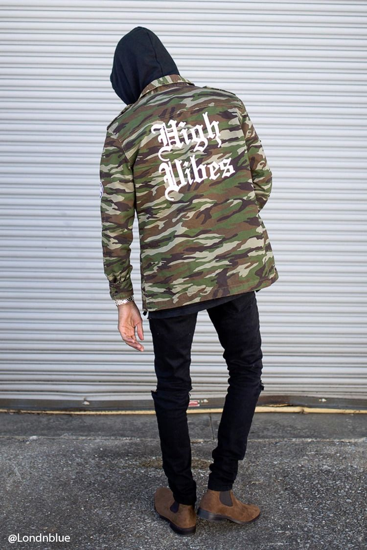 A Woven Camo Print Jacket Featuring An Old English High Vibes Graphic On Back Various Graphic Patches Throughout Long Camo Jacket Fashion Sweatshirt Jacket [ 1125 x 750 Pixel ]