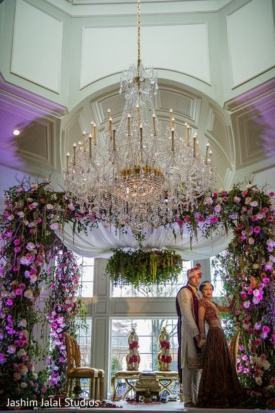 Floral mandap accented by a grand chandelier perfect modern indian floral mandap accented by a grand chandelier perfect modern indian wedding mandap junglespirit Image collections
