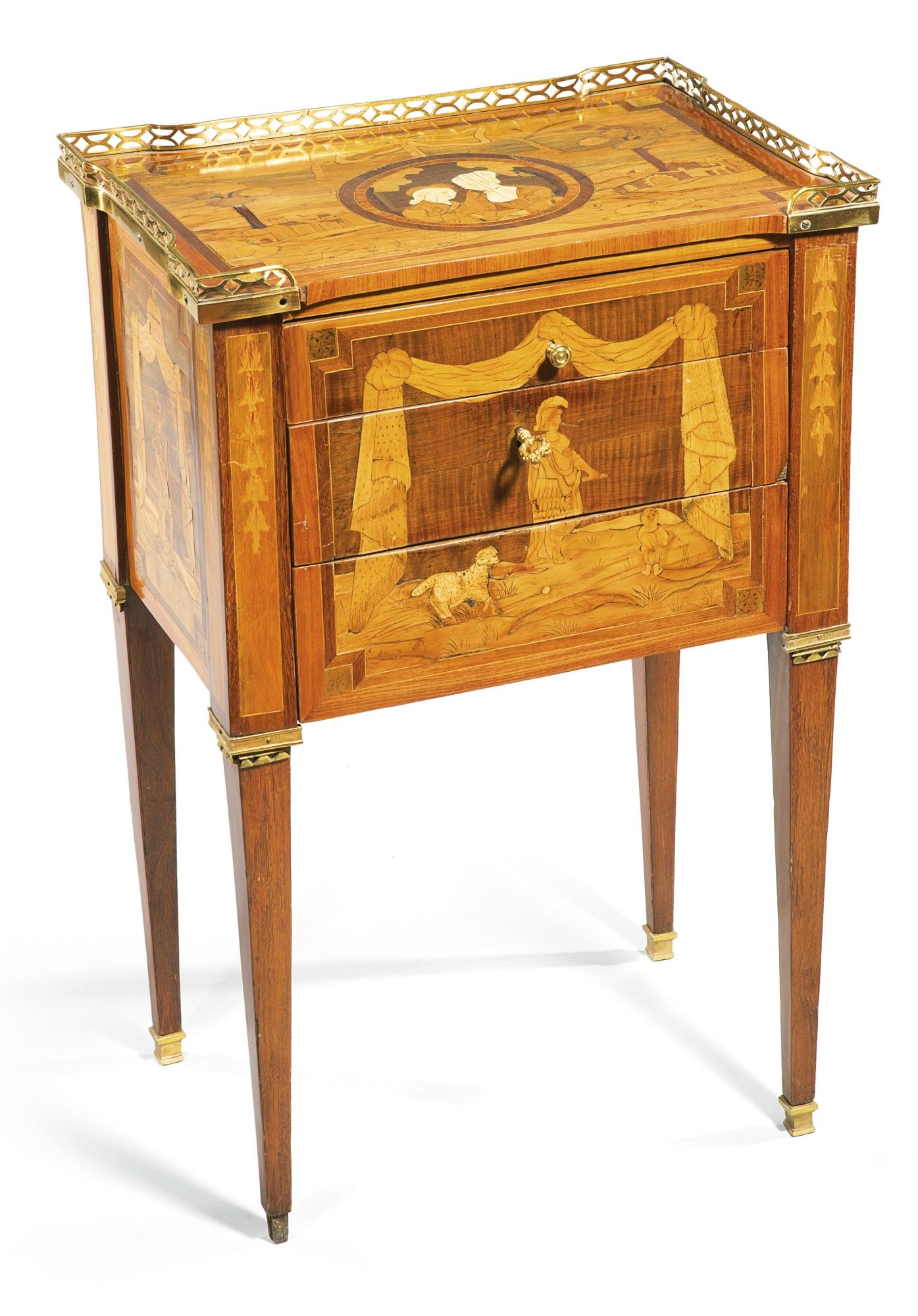 An ivory inlaid sycamore, fruitwood and amaranth marquetry table en chiffonière stamped Delorme, Louis XVI, circa 1780 the rectangular galleried top inlaid with a medallion of lovers with ivory faces set against a landscape, the front and sides with figures of Mars beneath drapery, with three drawers, the top one fitted for writing implements and a silk lined writing slide on square tapering legs headed by guttae, with gilt-bronze mounts throughout