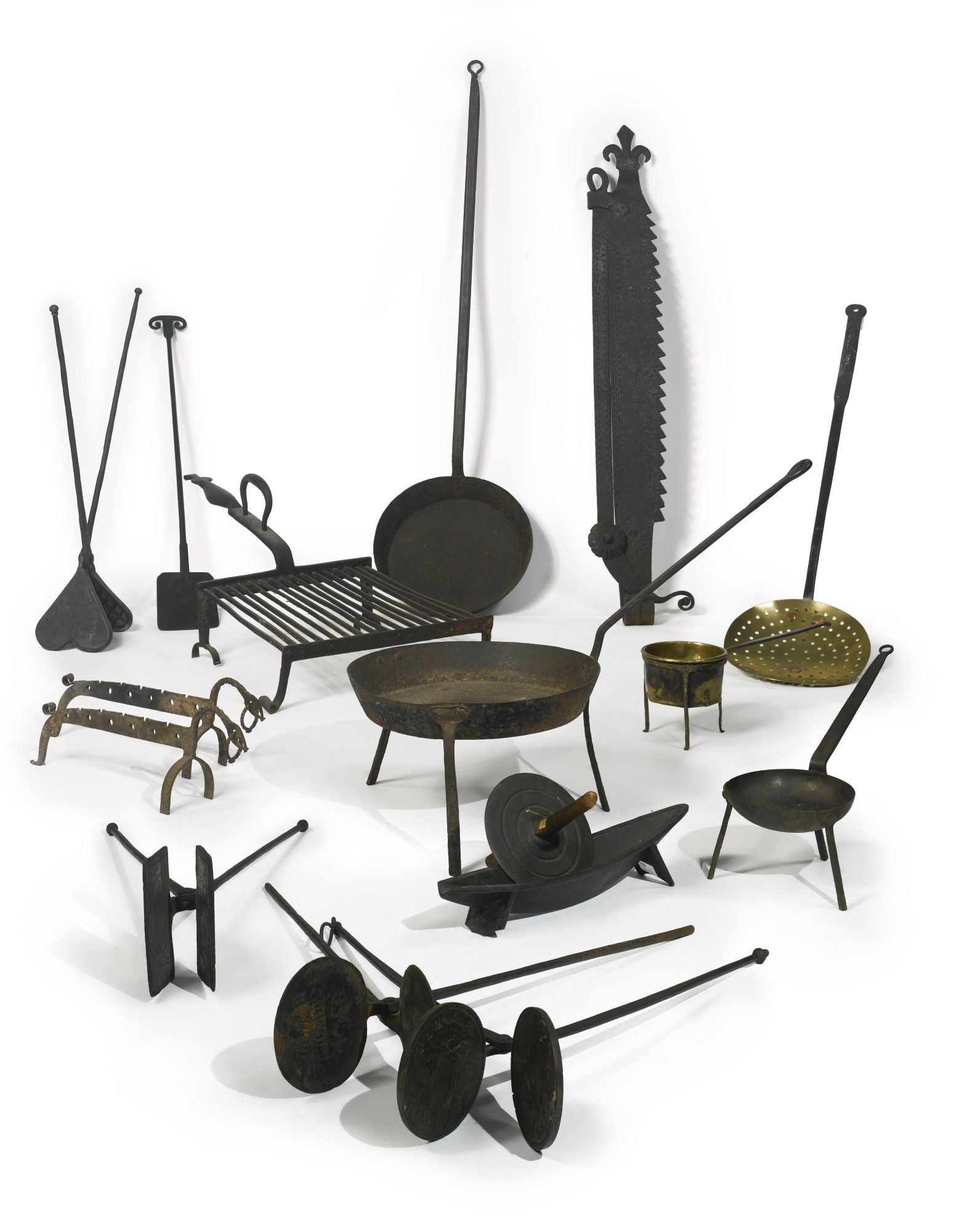 an assorted group of wrought and cast iron cooking implements