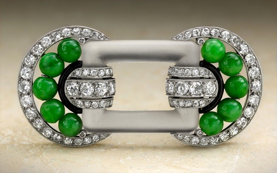 French, Art Deco brooch designed as two stylized circles of round diamonds, 10 jadeite jade spheres and black enamel, the two joined by frosted rock crystal, in platinum and 18K gold, circa 1925 With French hallmarks.