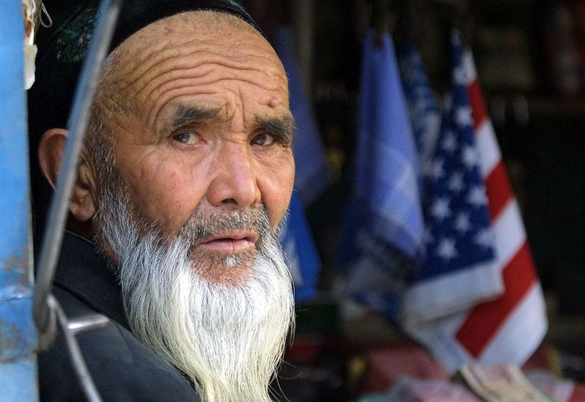 Muslim old man sells near the border with Afghanistan in the Chinese province Sing Uygur American flags.