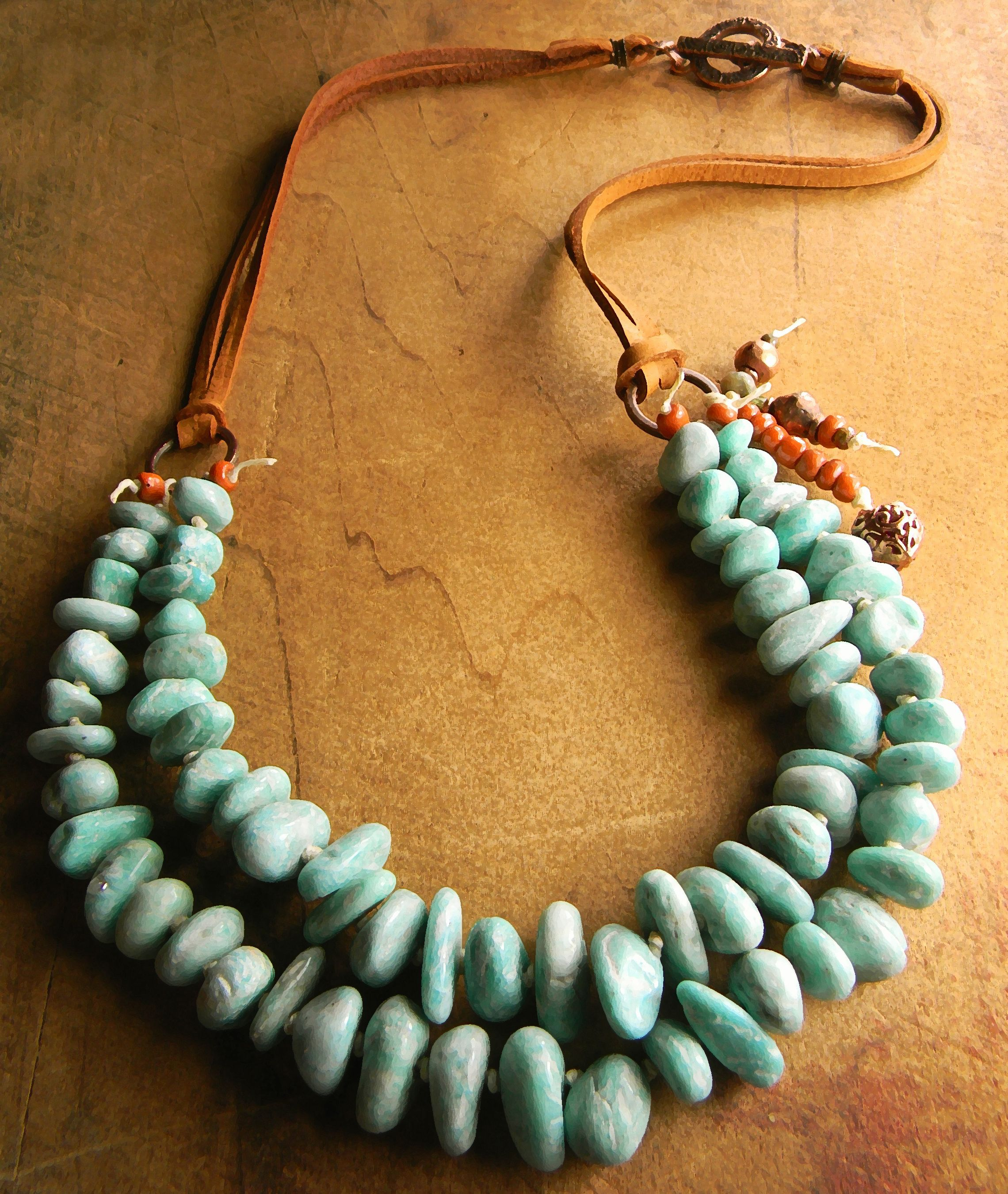 A boho southwestern necklace design with two strands of knotted amazonite nugget beads on Irish waxed linen cord. Russian green amazonite in a gorgeous shade of green accented by rusty orange Indonesian beads and copper with deerskin leather lacing to form the back of the necklace. An antiqued copper toggle is the perfect closure for this rustic necklace. The length is 20 inches.