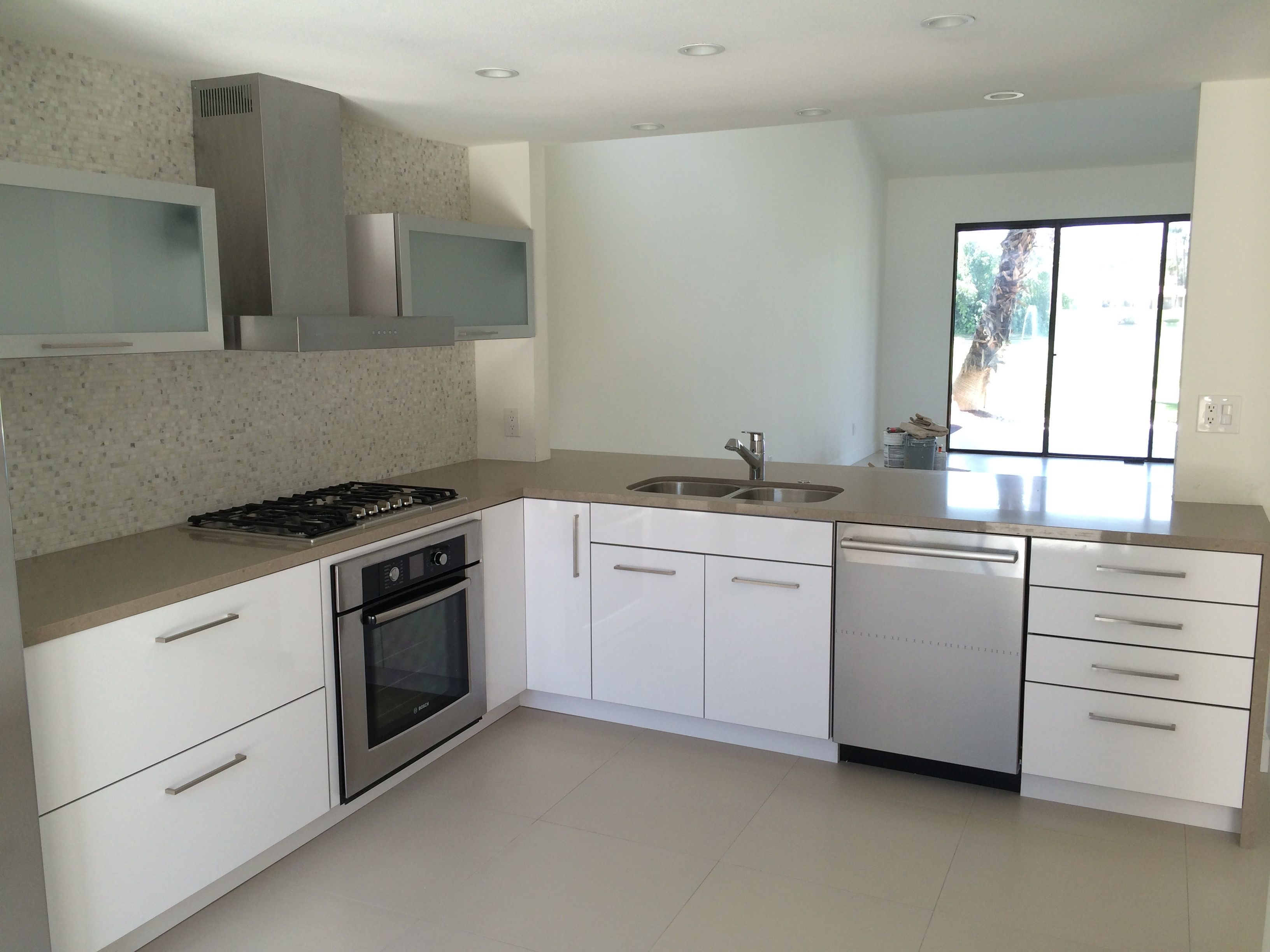 Contemporary white kitchen cabinets with tile back splash. Frosted front kitchen cabinets on either side of vent.