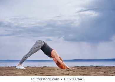 A middle-aged woman with red hair does gymnastics on the sandy shore of a large river. Cloudy spring...