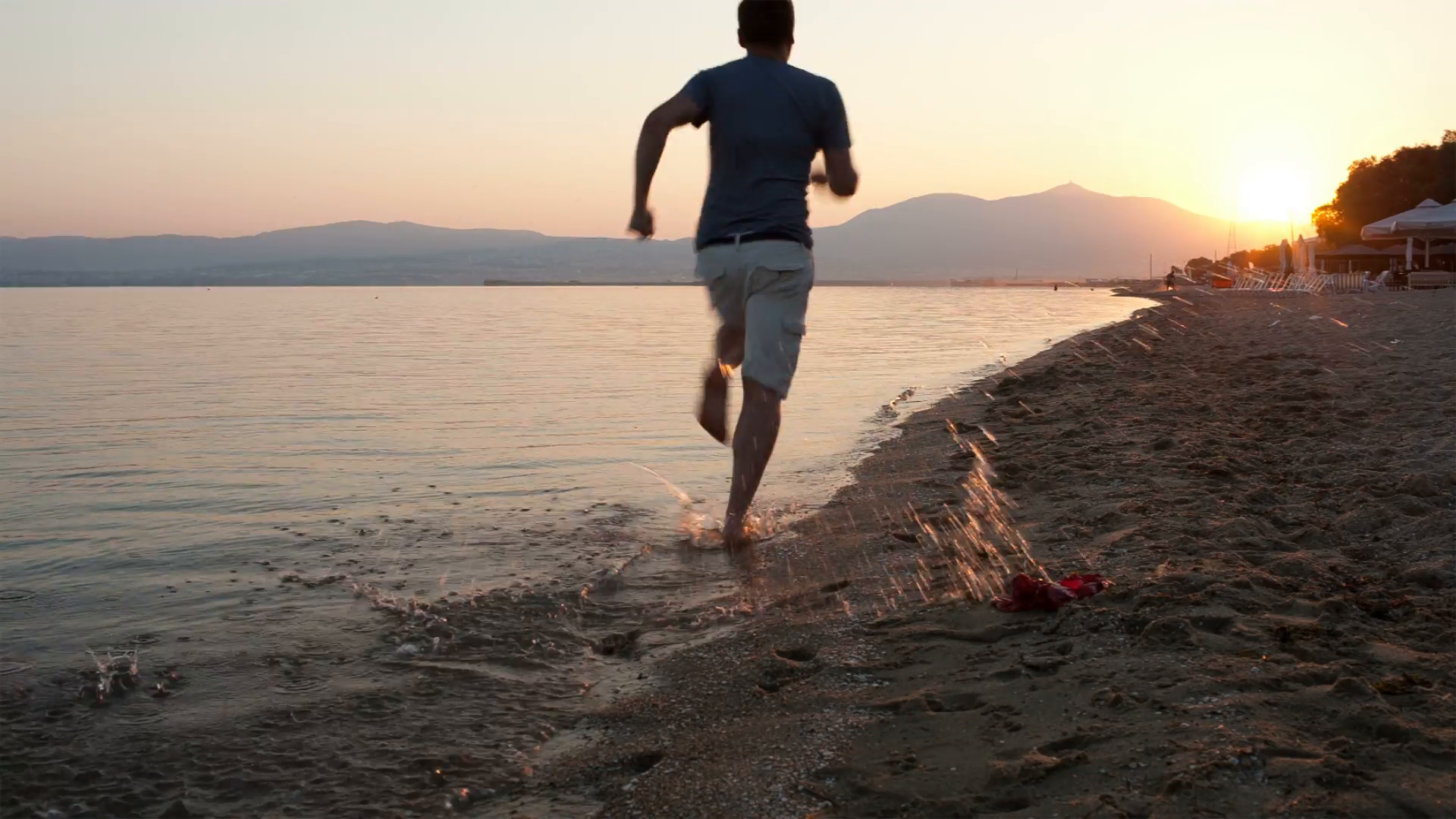Man Running Away From The Camera Along A Beach At The Edge Of The Sea Towards A Glowing Sunset As The Sun Dips Below Person Running Man Running Tropical Beach