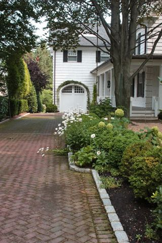 Brick driveway, beautiful garage door Gardens and Landscapes