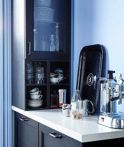 Kahvinkeitin kapealla työtasolla, kuppeja ja laseja seinäkaapissa.