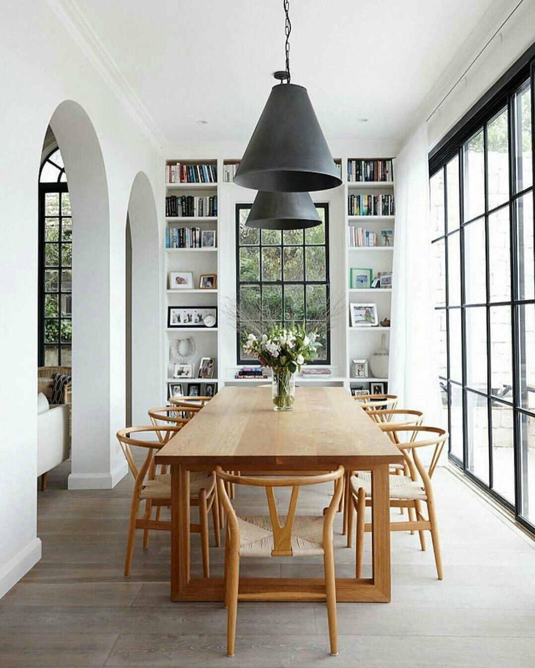 Modern Global Style Dining Room Design Featuring Built In Shelves A Large Wood Table Wishbone Side Chairs And Black Vintage Industrial Pendant Light