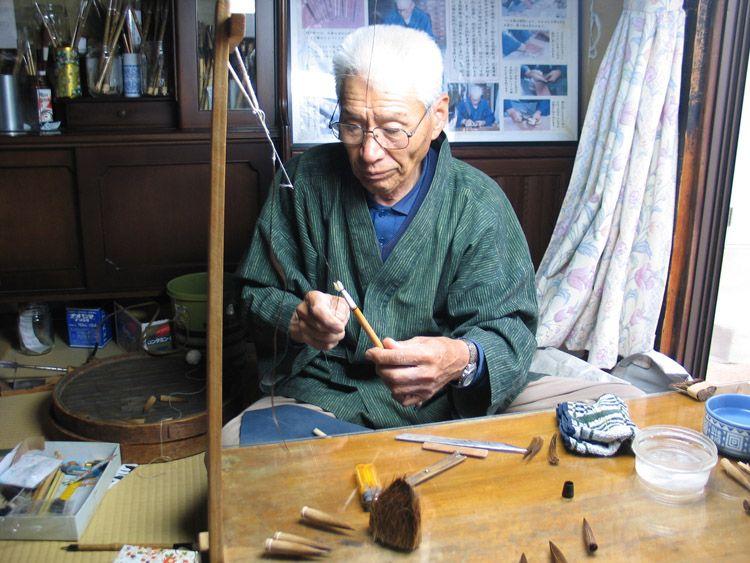 In zijn werkplaats aan huis fixeert Koso Aratani-san de puunt van een net gemaakt penseel. Kumano, Japan,16 juni 2015