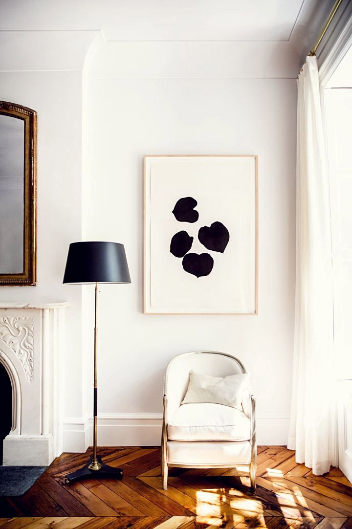 Sitting area by a big window with black and white art and floor lamp