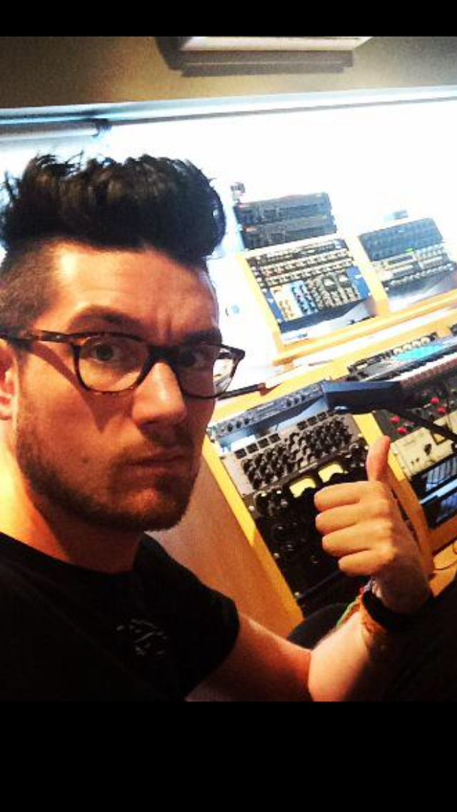 Dan Smith of Bastille, in glasses, making a face, pointing in studio