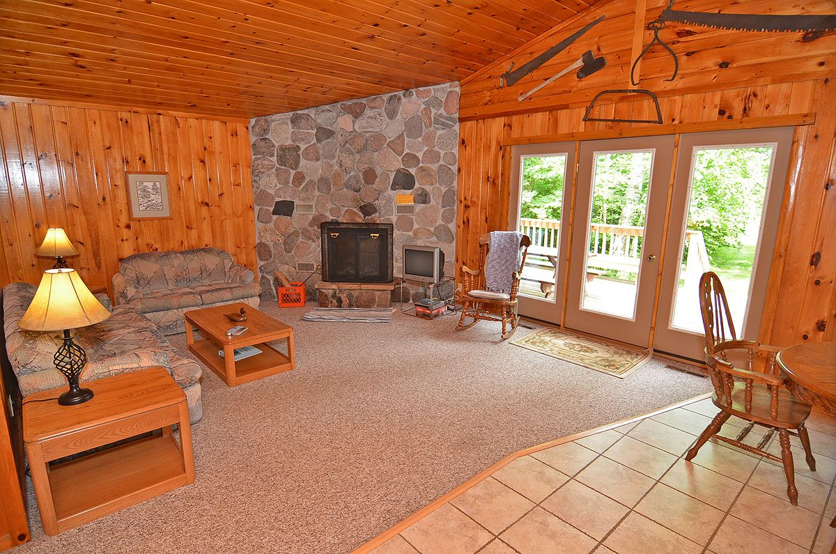 The 1200 square foot interior features knotty pine walls and ceilings and is tastefully decorated with northwoods décor the carpeted living room area with