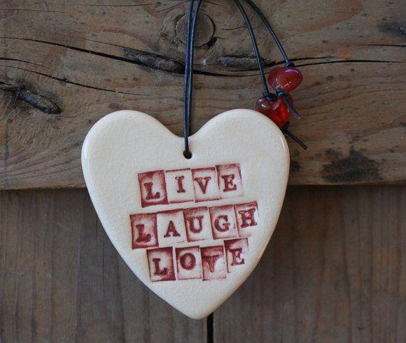 Les lettres de « Vivre lamour rire » a été individuellement imprimé dans ce cœur dargile et ensuite colorent lavés avec un décor sous glaçure rouge et