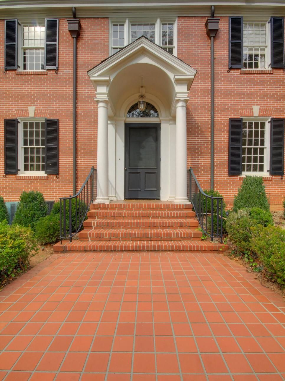The Black Front Door Gives A Stately Look To A Red Brick Home In A
