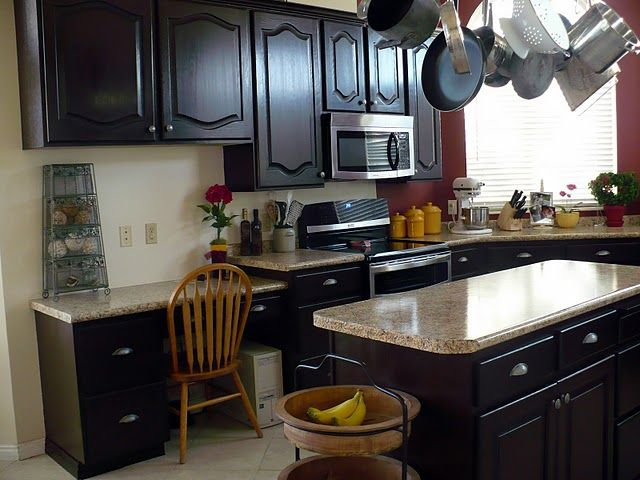 Lovely, inexpensive kitchen makeover. Refinished cabinets, bargain knobs, and faux granite counters.