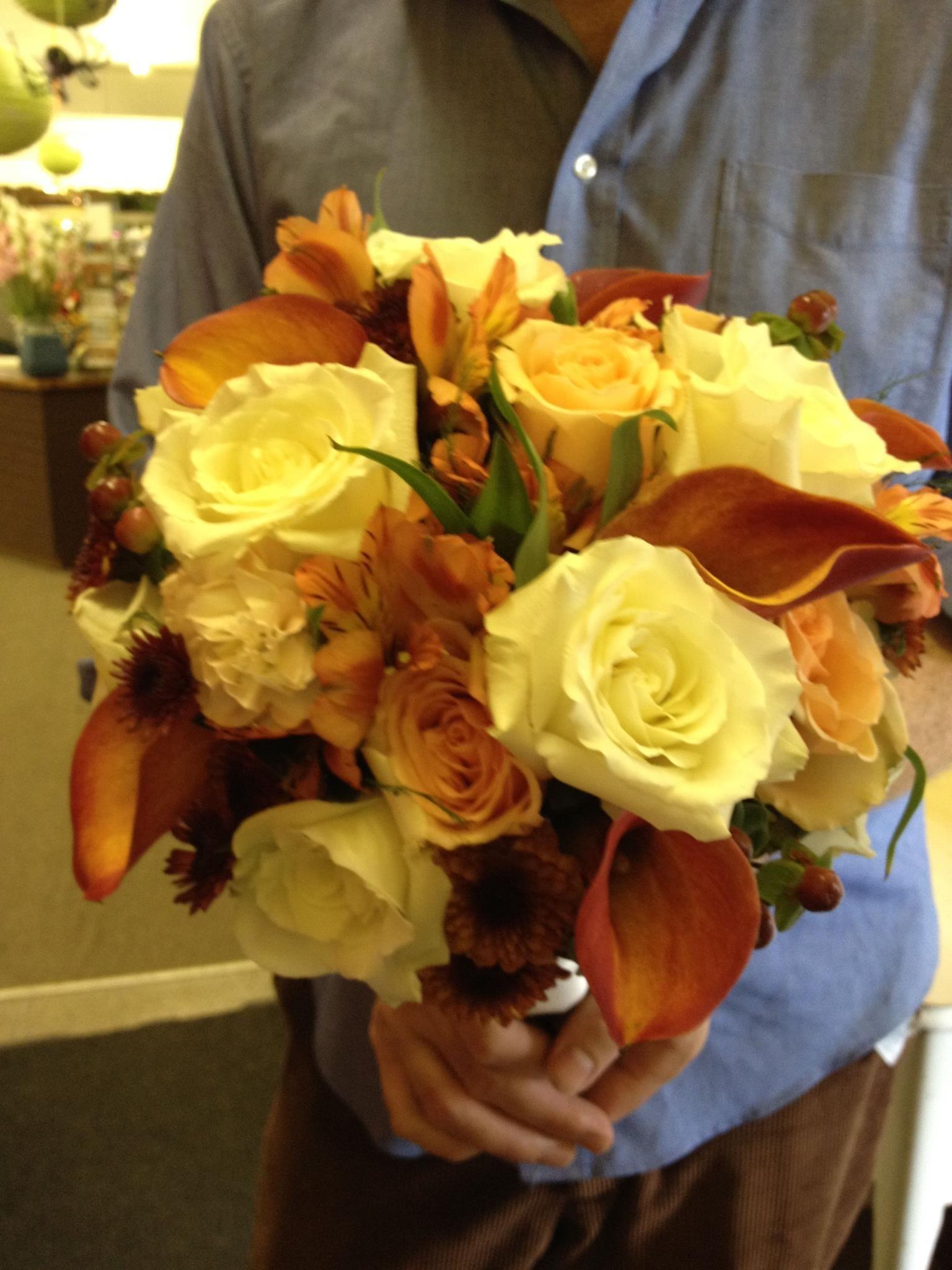 Fall bouquet of white roses, orange calla lilies, orange alstroemeria, orange roses, and hypericum berries