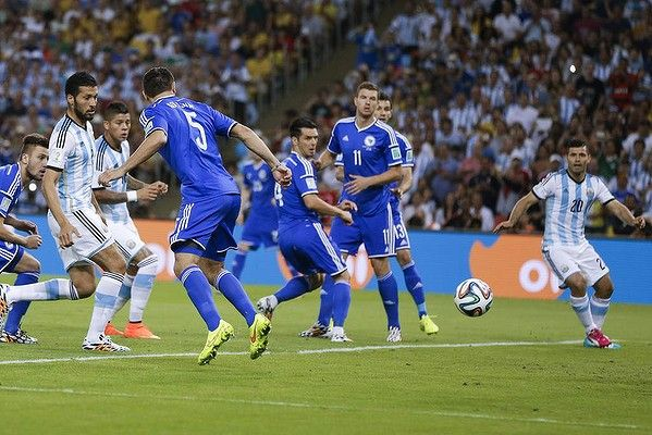 Argentine and Bosnian players watch as the ball bounces off of Bosnia's Sead Kolasinac for an own goal conceded in the second minute of the game.