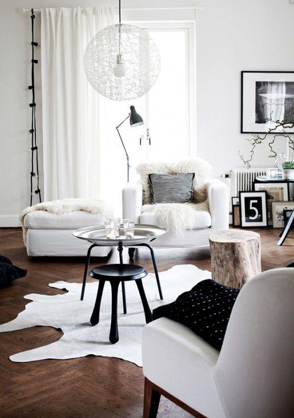 Salon scandinave  mur et mobilier blanc, peaux de bêtes et fausses