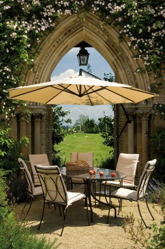 opulent grounds with stunning view  beyond archway.
