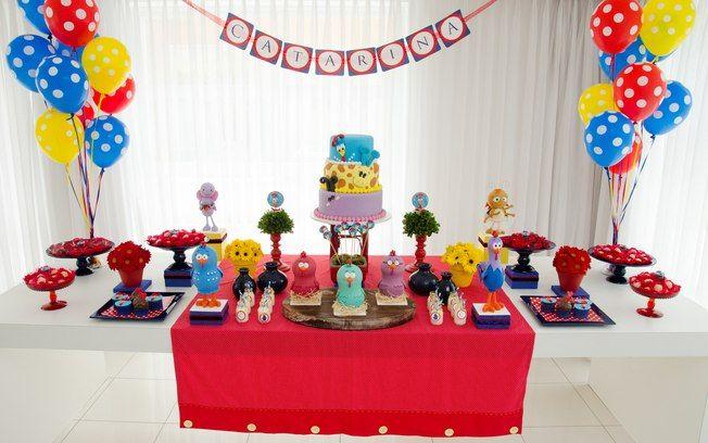 Veja como ficou a mesa completa. Arranjos de flores, caixas e docinhos circundam o bolo. Os vidrinhos ao centro foram servidos com leite, mas podem levar suco também