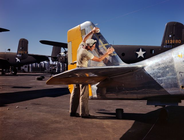 A painter cleans the tail section of a P-51 Mustang fighter prior to spraying it with olive-drab camouflage. North American Aviation plant, Inglewood, Calif., October 1942.